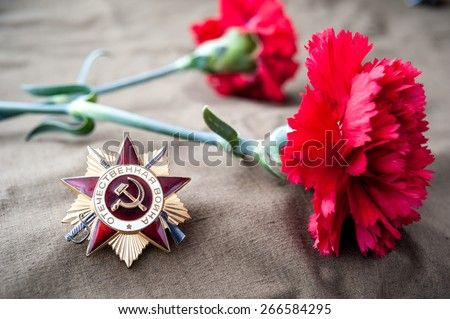 Order of the patriotic war 1st class and two red carnations. Still life dedicated to Victory Day. 9 May. - stock photo