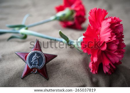 Order of the Red Star and two red carnations. Still life dedicated to Victory Day. - stock photo