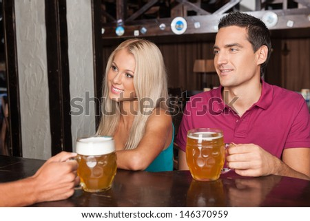 Ordering beer. Beautiful young couple ordering beer at the bar - stock photo