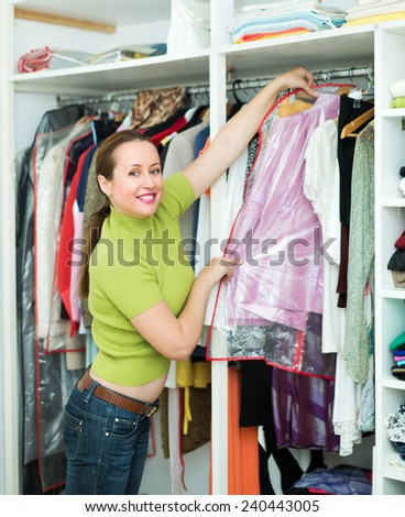 Orderly positive woman arranging clothes at wardrobe indoor - stock photo