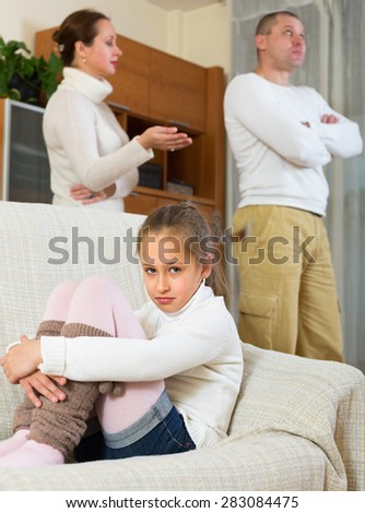 Ordinary adult couple with sad daughter on sofa having quarrel at home. Focus on girl - stock photo