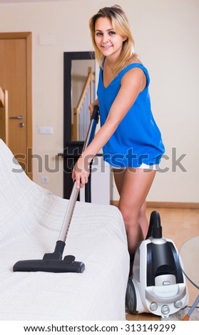 Ordinary adult russian housewife in casual hoovering at home and smiling