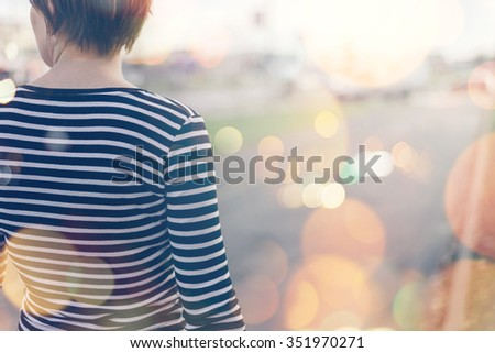 Ordinary casual woman from behind walking down the empty street on autumn afternoon, retro toned image with selective focus and bokeh light - stock photo