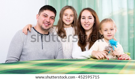 Ordinary cheerful family of four at table in living room at their home - stock photo