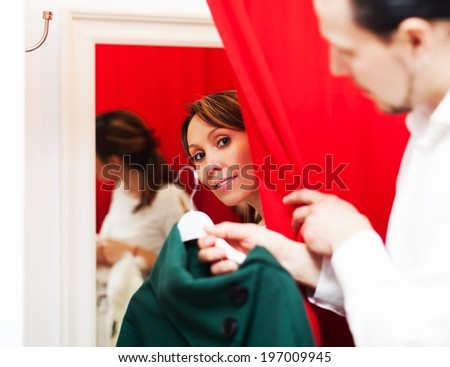 Ordinary couple choosing coat in fitting-room at boutique - stock photo