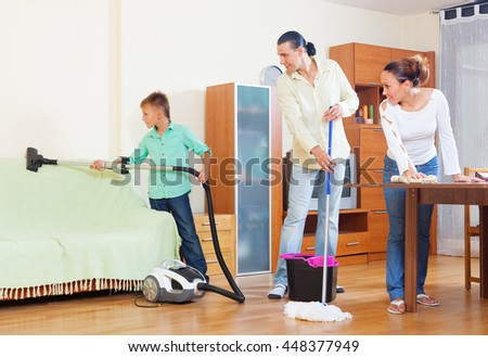 Ordinary family of three  doing house cleaning with  cleaning equipment