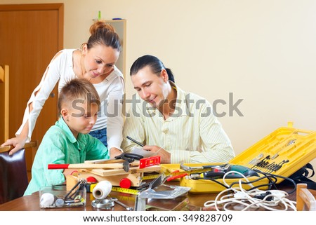 Ordinary family of three doing something with the working tools at home - stock photo