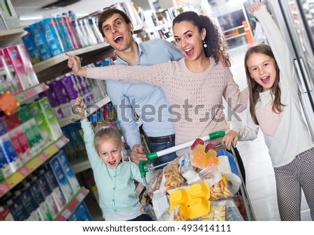 Ordinary family with daughters purchasing kefir in supermarket