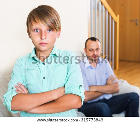 Ordinary father and his teenage son in the middle of argue in the home