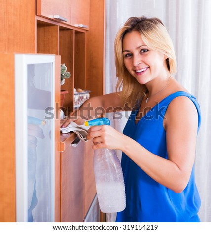 Ordinary girl in blue blouse dusting furniture indoors - stock photo