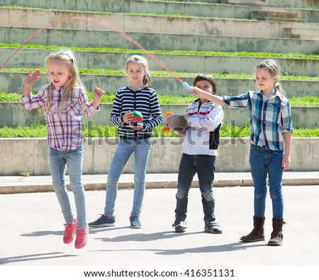 Ordinary girl jumping while jump rope game with friends outdoor - stock photo
