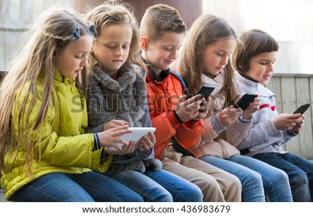 Ordinary kids sitting with mobile devices in street - stock photo
