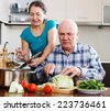 Ordinary mature couple cooking with vegetables in home kitchen - stock photo