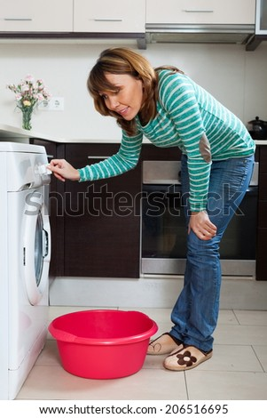 Ordinary woman in green doing laundry with washing machine at home