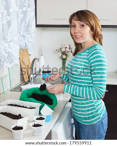 Ordinary woman in green making  ground  in pots for sprouts at table in home kitchen