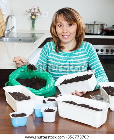 Ordinary woman in green making soil for seedling - stock photo
