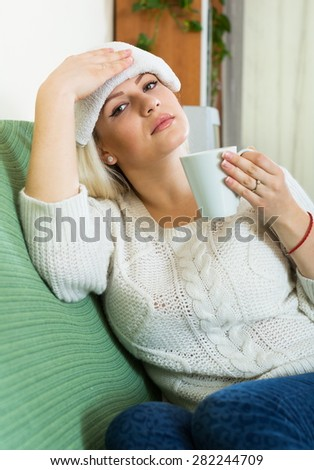 Ordinary woman with huge migraine holding wet towel on her head - stock photo
