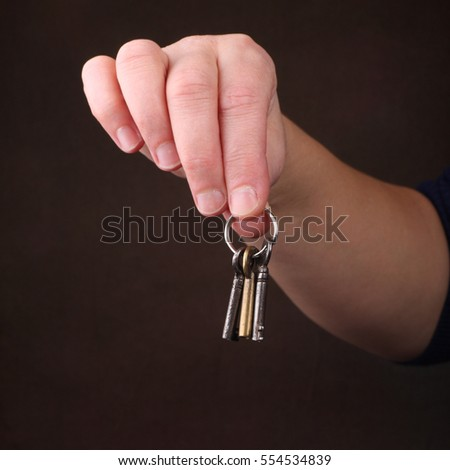 ordinary womans hands dangling a bunch of keys