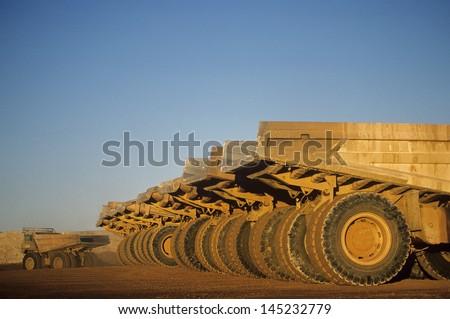 Ore hauling trucks in row Telfer Western Australia - stock photo