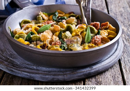 Orecchiette pasta of different colors with garlic and sage. Selective focus.