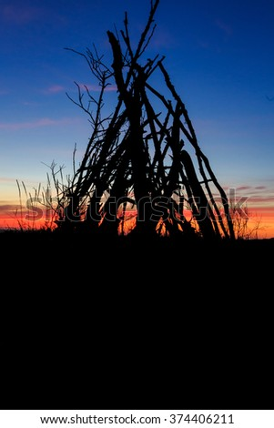 Oregon beach with a stick tipi at sunset along the coastline and a colorful sky. - stock photo