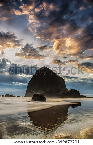 Oregon's Cannon Beach at sunset.  The iconic Haystack Rock stands tall - stock photo