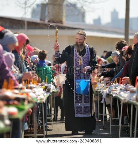 Orel, Russia, April 11, 2015: Traditional orthodox paschal ritual - priest blessing easter eggs and kulitches with holy water in blue bascket - stock photo