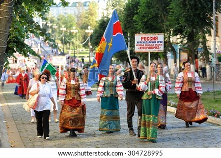 Orel, Russia, August 4, 2015: Orlovskaya Mozaika folk festival, men and women in Russian costumes marching with flag - stock photo