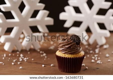 Oreo cupcake on white snow flakes Christmas background - stock photo