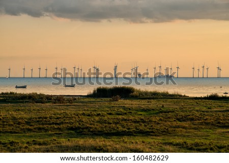 Oresund wind farm at dusk viewed from Bunkeflostrand south of Malmo, Sweden. The beach meadows in the foreground are several thousand year old pastures. - stock photo