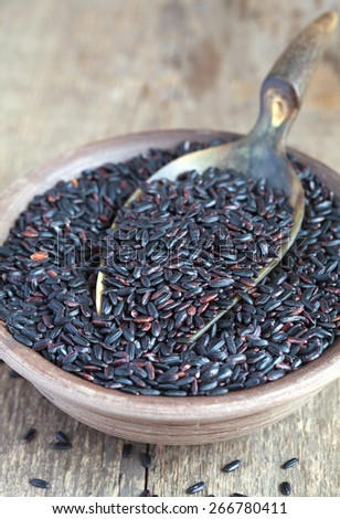 Organic Black Nerone Rice in a bowl on a wooden table,  selective focus - some grains in focus, some are not - stock photo