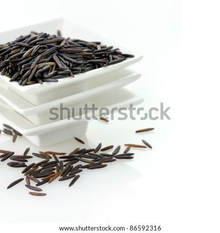 organic black rice in a white dish - stock photo