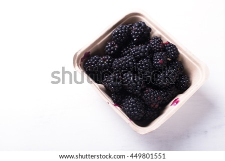 organic blackberries freshly harvested in a farmer's market container, isolated over white board, horizontal