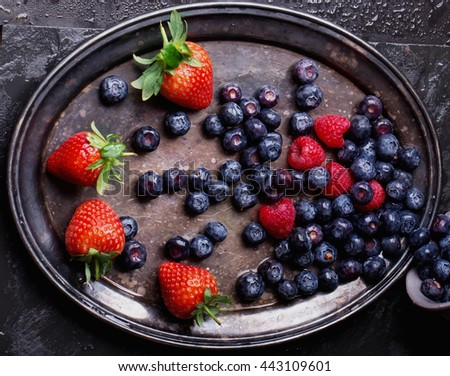 Organic blueberries served in the Vintage metal tray over a black slate board and dark metal background. Dark Rustic Style. Concept Healthy Food