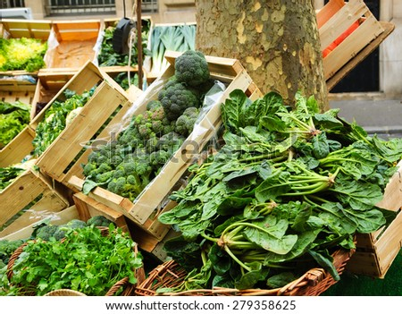 Organic broccoli, chard, parsley and other herbs and vegetables in wooden boxes and wicker baskets on the greengrocery stall at the farmers market in Paris. - stock photo