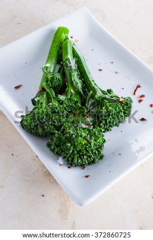 organic broccoli saut�©ed and seasoned with olive oil and red pepper flakes and sea salt served on a white plate - stock photo