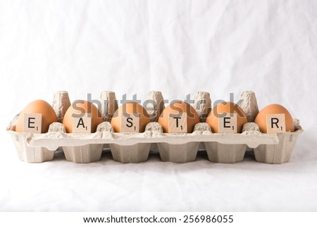 organic, brown eggs in a box, written easter with letters. isolated over a white background, horizontal - stock photo
