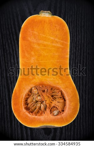 Organic butternut squash halved over black wood background