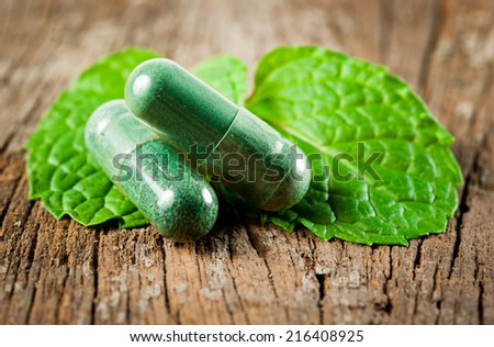 Organic capsule with mint leaves on wood - stock photo