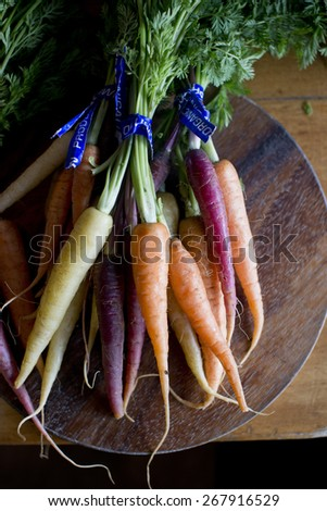 Organic Colored Carrots On Cutting Board - stock photo