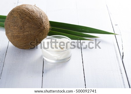 organic cosmetic cream and coconut on white wooden