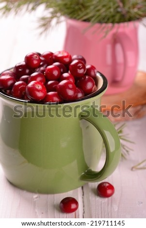 organic cranberries in the northern forest container on natural wooden table with pine branches alive selective focus.  - stock photo