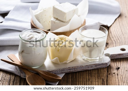 Organic dairy products on rustic wooden table. Cheese, milk, butter, sour cream - stock photo
