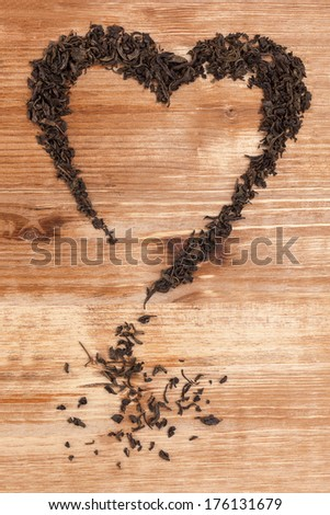 Organic dried green tea leaves in heart shape on wooden background. Traditional oriental beverage.   - stock photo