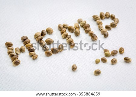 organic dried hemp seeds and word on white art canvas - stock photo