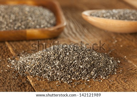 Organic Dry Black and White Chia Seeds against a background - stock photo