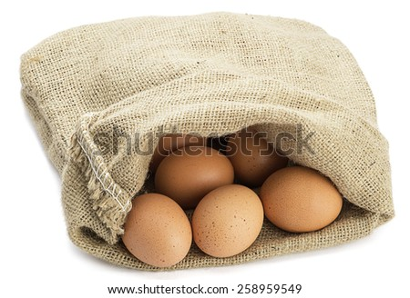 Organic eggs in jute sack isolated on white background. - stock photo