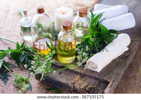 Organic essential aroma oil with  herbs on aged wooden background. Homeopathy. Selective focus.  - stock photo