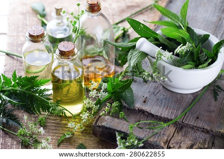 Organic essential aroma oil with mint  on aged wooden background. Selective focus.  - stock photo