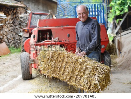 Organic farmer making/stack bales for feeding livestock. Model is a real farm worker!  - stock photo